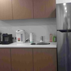 40A10_Pantry of business center. Modern design with office furniture provided. Equipped with a fridge and coffeemaker